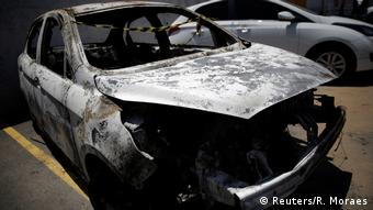 A burned car sits in the parking lot (Reuters/R. Moraes)