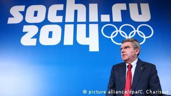 Томас Бах на фоне логотипа Олимпиады в Сочи