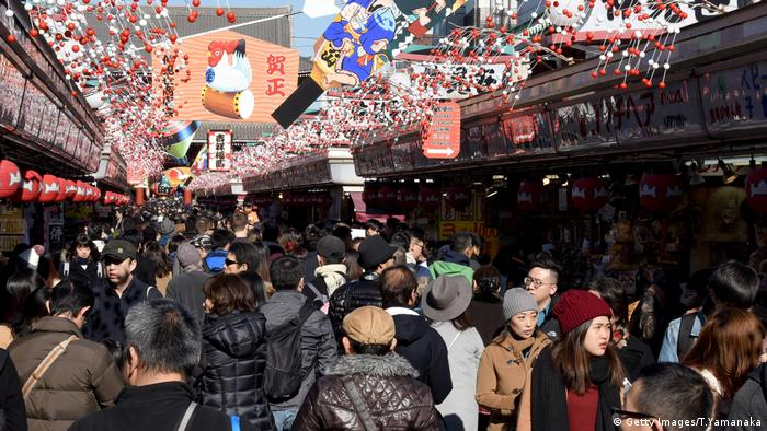 People walk underneath ornaments as they visit the Sensoji temple in Tokyo on New Year's Eve (Getty Images/T.Yamanaka)