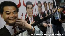 01.01.2017 A protester raises a picture of Chief Executive Leung Chun-ying, left, with devil horns during a protest on the first day of 2017 in Hong Kong, Sunday, Jan. 1, 2017. They protest against Beijing's interpretation of Basic Law and Hong Kong government's bid to ban pro-democracy lawmakers from taking office. They also demand true universal suffrage, which is not happening in the coming chief executive election in March. (AP Photo/Vincent Yu) |