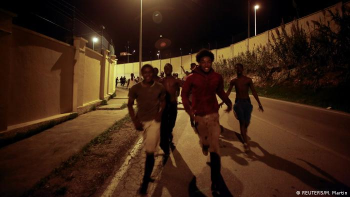 African migrants run on a road after crossing the border fence between Morocco and Spain's north African enclave of Ceuta, December 9 (REUTERS/M. Martin)
