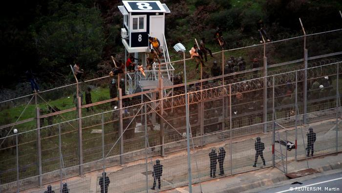 Migrants sit on the fence between Morocco and Ceuta during a December 9 assault on the border