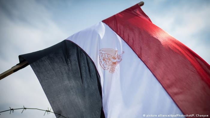 Egypt's national flag hangs on barbed wire outside the Cairo Police Academy