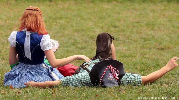 man and woman sit and lie on a lawn (picture alliance/dpa/R. Peters)