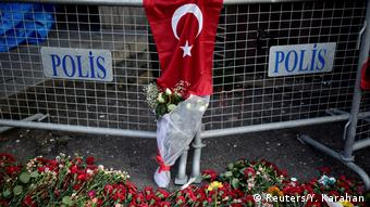 Flowers lay in front of a police barrier near the nightclub