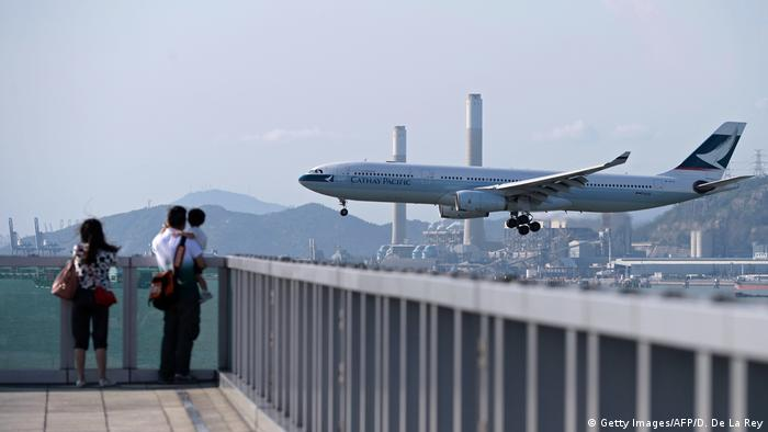 People watch as a Cathay Pacific passenger plane prepares to land at Hong Kong's international airport
