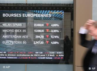 A man walks past a screen showing the European stock markets fall in Paris