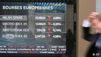 A man walks past a screen showing the European stock markets fall in Paris, Wednesday, Oct. 8, 2008.