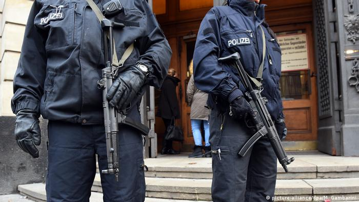 Two German police officers stand outside a building in Berlin (picture-alliance/dpa/M. Gambarini)