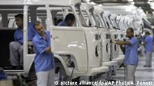 Men work at the assembly line of the Volkswagen van known in Brazil as Kombi in Sao Bernardo do Campo, outskirt of Sao Paulo, Brazil, Monday, Dec. 9, 2013. Brazil is the last place in the world still producing the iconic vehicle but VW says production will end Dec. 31. Safety regulations mandate that every vehicle in Brazil must have air bags and anti-lock braking systems starting in 2014, and the company says it cannot change production to meet the law. (AP Photo/Andre Penner) |