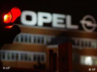 Red traffic light outside opel plant at night