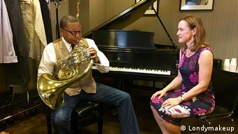 Sarah Willis trifft Wynton Marsalis, playing into a tuba and sitting in front of a piano (Londymakeup)