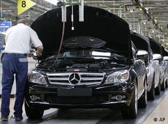 A Mercedes-Benz employee controls a Mercedes C-class as it rolls off the production line