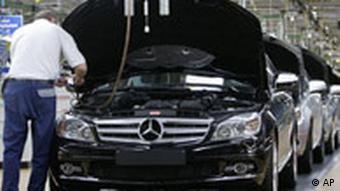 Worker checking car in Daimler factory in Stuttgart, Germany