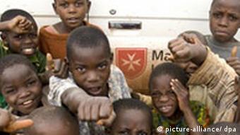 Kinder vor einem Fahrzeug des Malteser Hilfsdienstes