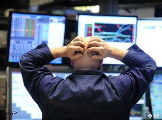 Specialist Justin Bohan holds his head as he works at his post on the floor of the New York Stock Exchange, Thursday Oct. 9, 2008. Stocks plunged in the final minutes of trading Thursday, sending the Dow Jones industrials down more than 675 points, or more than 7 percent, to their lowest level in five years after a major credit ratings agency said it was considering cutting its rating on General Motors Corp. (AP Photo/Richard Drew)