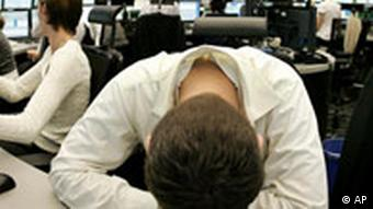 A stock trader in Frankfurt with his head down on a desk
