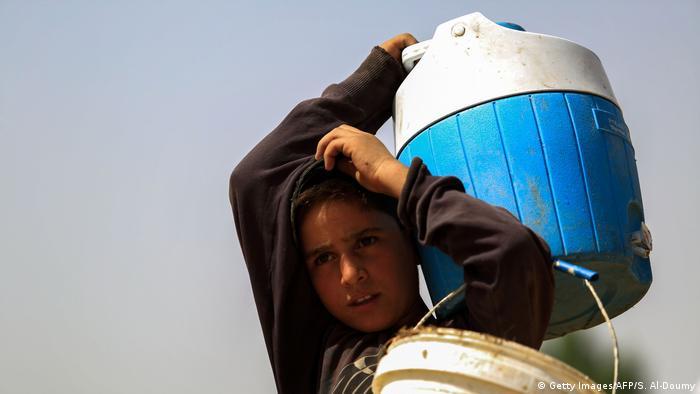 Menino carrega recipientes com água sob o sol