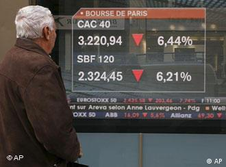 A man looks at a screen displaying market news in Paris