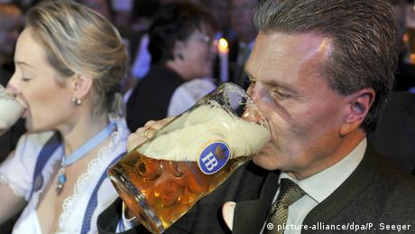 Günther Oettinger drinks a tankard of beer