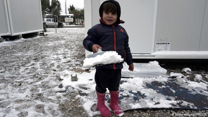 Child with dustpan full of snow on Lesbos (Getty Images/AFP/STR)