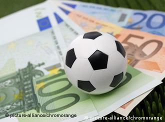 Euro bills under a mini soccer ball