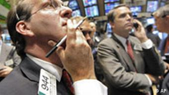 Traders at the New York Stock Exchange look up