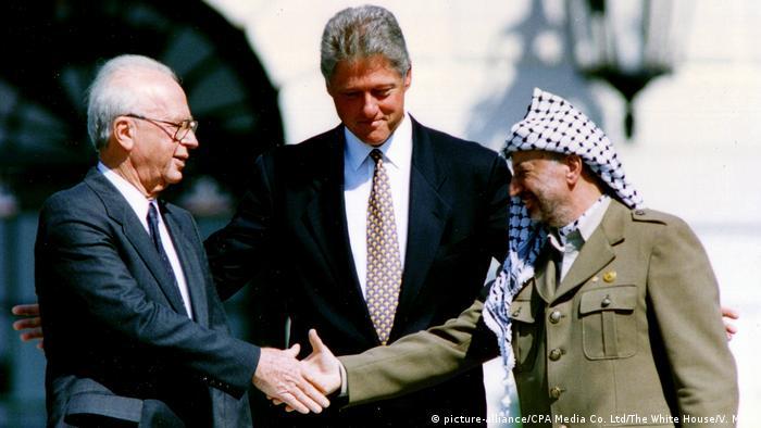 Ицхак Рабин и Ясер Арафат си подават ръка под погледа на Бил Клинтън