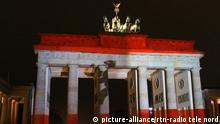Nach den Terror Anschlag in Berlin trauern die Menschen, legen Blumen nieder und zuenden Kerzen am Breitscheidplatz. Das Brandenburger Tor wurde in den Farben Deutschlands und Berlin angestrahlt | Verwendung weltweit