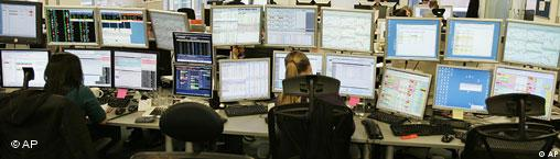 Image of stock traders looking at a series of computer screens on trading floor