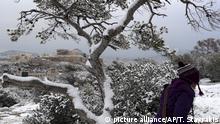 10.1.2017**dpatopbilder - Der Parthenon Tempel ist am 10.01.2017 auf dem schneebedeckten Hügel der Akropolis in Athen (Griechenland) zu sehen, im Vordergrund geht eine Frau spazieren. Etliche Dörfer und auch Inseln sind nach schweren Schneefällen seit zwei Tagen von der Außenwelt abgeschnitten. Auf Kreta wurden minus 15 Grad gemessen. Foto: Thanasssis Stavrakis/AP/dpa +++(c) dpa - Bildfunk+++ |