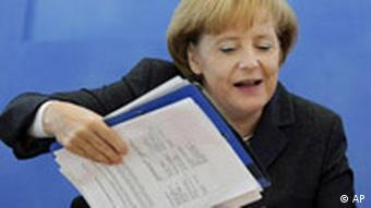 Die CDU-Vorsitzende und Bundeskanzlerin Angela Merkel legt am Montag, 13. Okt. 2008, vor Beginn einer Sitzung des CDU-Bundesvorstands in Berlin ihre Unterlagen auf den Tisch. (AP Photo/Miguel Villagran) --- Angela Merkel, German Chancellor and Chairwoman of the Christian Democratic Union CDU party, prepares her documents as she attends a party leaders' meeting in Berlin, Monday, Oct. 13, 2008. (AP Photo/Miguel Villagran)