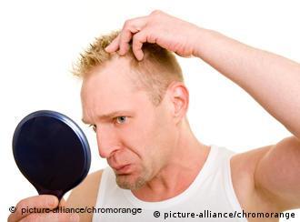 Ein Mann schaut sich seine Haare in einem Handspiegel an
