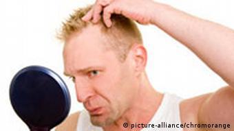 Blonder Mann betrachtet besorgt seine Haare im Spiegel (picture-alliance/chromorange)