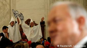 Protesters dressed as KKK members interrupt Sessions' hearing