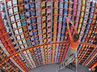 A woman on a ladder sorts books arranged on a very high wall