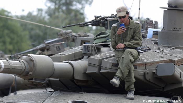 Israeli soldier checks his phone while sitting on a tank.