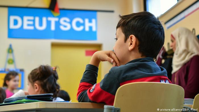 Criança sentada numa sala de aula, com a mão no queixo, vista por trás. No fundo, a palavra deutsch, outros alunos e uma mulher de véu islâmico