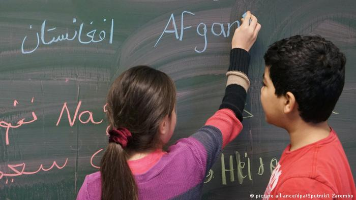 Refugee children write on the board in class