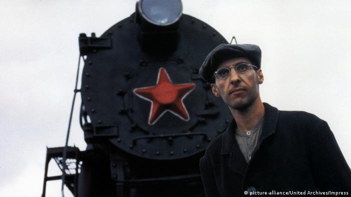 Filmstill aus Die Atempause zeigt einen Bahn mit runder Brill und einer Barrettmütze in schwarzen Mantel, hinter ihm ist eine Dampflock mit einem roten Stern zu sehen (Foto: picture-alliance/United Archives/Impress).