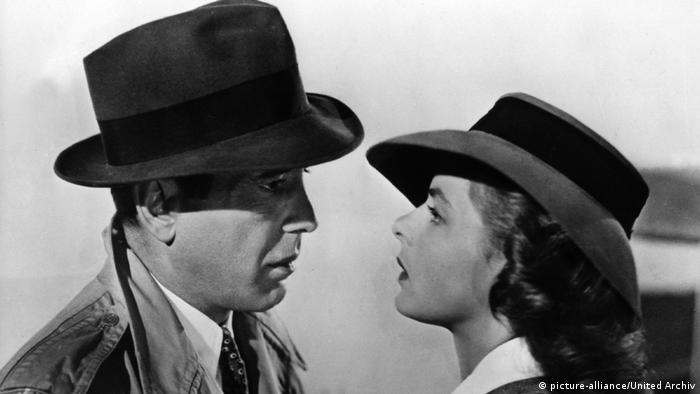 Filmszene aus Casablanca: Humphrey Bogart (links) schaut Ingrid Bergman (rechts) ganz tief in die Augen. Beide tragen einen Hut und einen Mantel. (picture-alliance/United Archive)