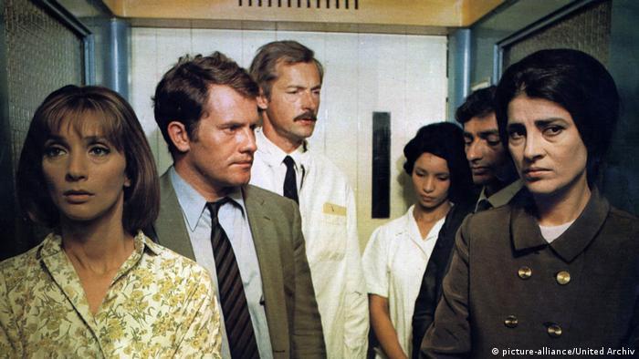 Szene aus Costa-Gavras' Film Z: drei Männer und drei Frauen schauen konsterniert in einem engen Raum