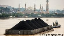 SAMARINDA, INDONESIA - AUGUST 26: A tug pulls a coal barge past the Islamic centre on August 26, 2016 in Samarinda, Kalimantan, Indonesia. Indonesia's East Kalimantan was reported to be one of the worst affected province when coal prices dropped from a high of over USD 127.05 per metric ton in 2011 to the current price of around USD 50 per metric ton in August 2016. Commodity-rich towns in Kalimantan, the world's largest exporter of thermal coal, were hit hard when coal mining companies ceased operations which created a lack of job opportunities and severe social implications, such as an increase in drug abuse and prostitution, as miners found difficulties in finding job opportunities. As the number of unemployment rises in coal mines at parts of Indonesia, both foreign and local workers return home leaving some villages with 50 percent less population leaving abandoned housing and infrastructures while construction sites have been left delayed or cancelled. (Photo by Ed Wray/Getty Images)