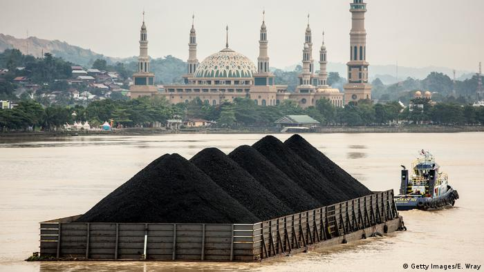 A tug tows a coal barge past the Islamic centre on August 26, 2016, at Samarinda, Kalimantan, Indonesia (Getty Images/E. Wray)