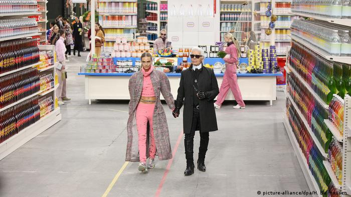 Karl Lagerfeld and Cara Delevigne on a catwsalk that looks like a supermarket aisle. (picture-alliance/dpa/H. Ballhausen )