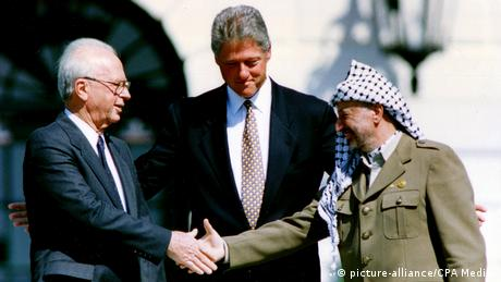 Israeli Prime Minister Yitzhak Rabin und PLO Chairman Yasser Arafat shake hands as President Bill Clinton looks on (picture-alliance/CPA Media )