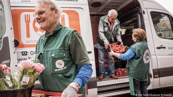 people unloading food from van
