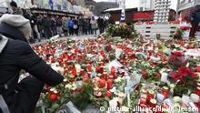 ARCHIV - Besucher stehen am 22.12.2016 in Berlin nach der Wiedereröffnung des Weihnachstmarktes am Breitscheidplatz hinter Blumen und Kerzen. Der Tunesier Amri steuerte am 19.12.2016 einen gestohlenen Lkw auf den Weihnachtsmarkt und tötete dabei zwölf Menschen. (zu dpa-KORR «Vier Wochen nach dem Berliner Anschlag: Wo kann ich helfen?» vom 13.01.2017) Foto: Rainer Jensen/dpa +++(c) dpa - Bildfunk+++ | Verwendung weltweit