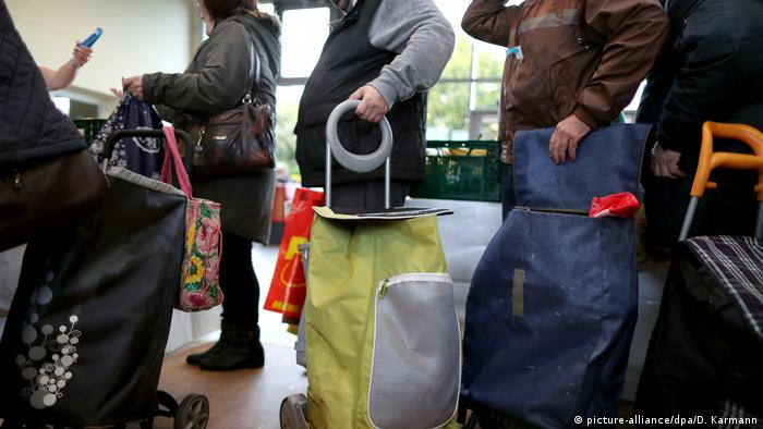 people standing in line with large bags