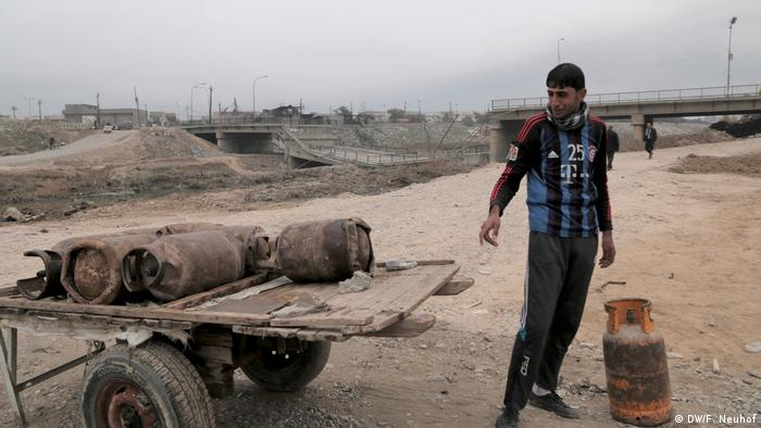 A man sells gas canisters in front of a destroyed bridge in eastern Mosul